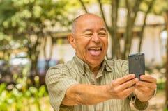 Plenerowy widok stary człowiek wtyka out jęzor z telefonem komórkowym w jego rękach siedzi na ławce robi wideo krzywka, otaczać Obraz Royalty Free
