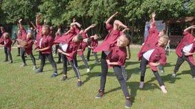 Plenerowy występ, kreatywnie drużyna tanczy w identycznym odziewa na tle zieleni drzewa przy wakacyjnym wydarzeniem w parku zbiory wideo