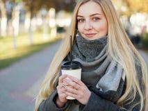 Plenerowy zakończenie w górę strzału 20s roku blondynki elegancka kobieta pije kawę lub herbaty iść w szaliku na przerwie na lunc zdjęcia stock