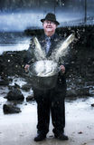 Plentitude And Abundance. Senior Man Holding A Bucket Filled With Splashing Water And Jumping Fish Standing On A Seaside Shoreline In A Depiction Of Plentitude Royalty Free Stock Images