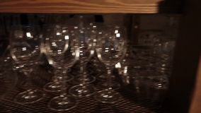 Plenty of empty glasses at bar. Close up shot of a dozens of empty glasses and bottles standing at the bar in a restaurant. Equipment for bartender stock video