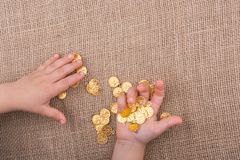 Plenty of fake gold coins in hand stock photography