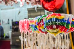 Clown inspired lollipops for sale in the market. Plenty of lollipops in the colours of the rainbow waiting to be sold at the market stall Stock Photos