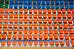 Plenty of orange and blue plastic seats at stadium . Royalty Free Stock Image