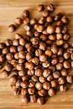 Plenty of organic hazelnuts on wooden cutting board Royalty Free Stock Image