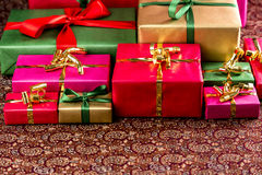 Plenty of Presents Ready to be Collected. Plain-colored gifts lined up for the handing out of presents. Wrapped in vibrant red, magenta, green and gold. Shallow Royalty Free Stock Photos