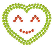 Plenty of red and green pills shaped in heart form with happy face sign inside Royalty Free Stock Photography