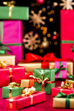 Plenty of Single-Colored Xmas Presents. Many plain Christmas gifts arranged on a red cloth. Narrow depth of field. Mostly soft shapes in vibrant colors Stock Images