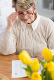 Plenty of time to devote to what she likes most. Portrait of an elderly lady wearing glasses, reading a magazine at a table decorated with yellow tulips Royalty Free Stock Image