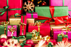 Plenty of Xmas Gifts Piled Up. Multitude of Christmas presents waiting to be handed out. Wrapped in single colors. Red, green, gold and magenta. Blurred baubles Stock Photography