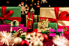 Plenty of Xmas Gifts in Red, Gold and Green. Many plain Christmas presents piled up on a red cloth. All with unicolored bows in red, green and gold. Narrow depth Stock Images
