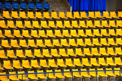 Plenty of yellow and blue plastic seats at stadium . Stock Photo