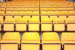 Plenty of yellow plastic seats at stadium Stock Images