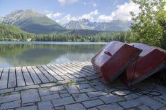Pleso Strbske, υψηλά βουνά Tatras, Σλοβακία, πρωί αρχών του καλοκαιριού, αντανακλάσεις λιμνών, κόκκινες βάρκες στην ξύλινη αποβάθ Στοκ εικόνα με δικαίωμα ελεύθερης χρήσης