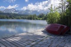 Pleso Strbske, υψηλά βουνά Tatras, Σλοβακία, πρωί αρχών του καλοκαιριού, αντανακλάσεις λιμνών, κόκκινες βάρκες Στοκ Φωτογραφίες