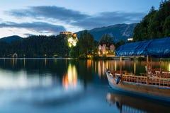 Pletna στη λίμνη που αιμορραγείται στο σούρουπο, Σλοβενία Στοκ Εικόνες