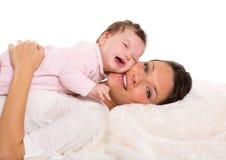 Pleurer et mère de bébé se trouvant ensemble sur la fourrure blanche photo stock