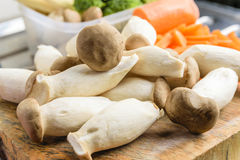 Pleurotus eryngii. King oyster mushroom, Pleurotus eryngii on chopping wood board and many kind of vegetables in background Royalty Free Stock Image