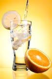 Pleuvoir à torrents de l'eau minérale en glace avec le citron photo stock