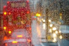 Pleuvoir dans la vue de Londres à l'autobus rouge par la fenêtre pluie-tachetée Photos stock