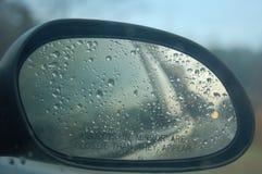 Pleuvoir dans le miroir de côté droit de la voiture avec le ciel en vue photos stock