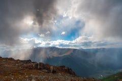 Pleuvoir dans les montagnes avec une lueur de ciel bleu Photos stock
