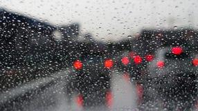 Pleuvoir de l'eau de baisse et l'embouteillage rouge de bokeh sont dessus montés la manière, concept de fond photos stock
