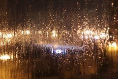 Pleuvoir en dehors de la fenêtre dans la ville de soirée image libre de droits
