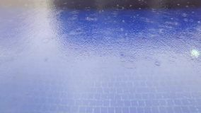 Pleuvoir la chute dans la piscine bleue banque de vidéos