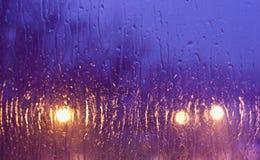 Pleuvoir les baisses sur l'hublot au fond de lumière de nuit images stock