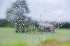 Pleuvoir les baisses sur la fenêtre et le paysage rural trouble photographie stock
