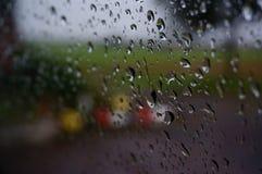 Pleuvoir les baisses sur un vitrail sur un fond brouillé image libre de droits