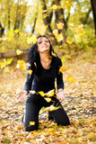 pleying黄色的女孩愉快的叶子 免版税库存图片