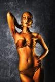 plezier Glanzende Vrouw met Gouden Lichaamsart. glamor Op de achtergrond van grijze muur stock fotografie