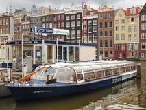 Plezierboot dichtbij de pijler in Amsterdam. Nederland Royalty-vrije Stock Afbeeldingen
