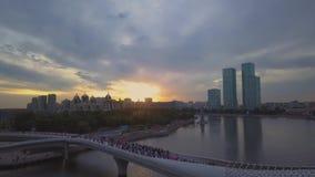 Plezierboot die onder de brug in de achtergrondzonsondergang, Astana varen stock footage