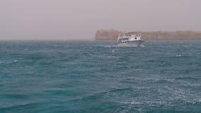 Plezierboot met toeristenzeilen in het stormachtige overzees op de achtergrond van rotsen Egypte stock footage