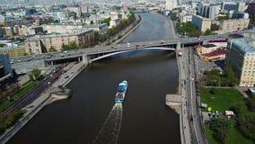 Plezierbootvlotter of het gaan onderaan de rivier in stad of megapolis Satellietbeeld van blauwe en witte boot met mensen Boot stock footage