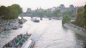 Plezierboten cruisingl op de Zegen in de avond in Parijs, mensen die op de waterkant zitten stock footage