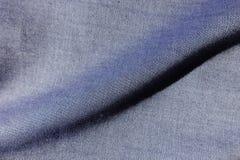 Pli diagonal sur le tissu de blues-jean images stock