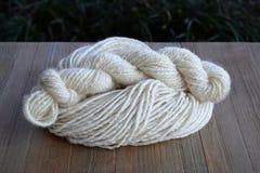 Plied Yarn Skein on a Pile of Hand Spun Yarn Royalty Free Stock Photo
