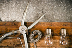 Pliers, bulbs, rope, key, hanging on nails on the old wooden stand closeup Stock Photography