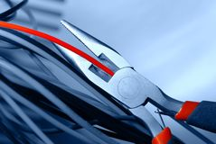 Pliers and cable. Pliers cut the red cable Royalty Free Stock Images