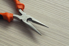 Pliers closeup on wooden background. Extreme close up Royalty Free Stock Photo