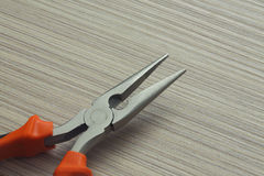 Pliers closeup on wooden background. Extreme close up Royalty Free Stock Image
