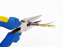 Pliers cutting a cable. Needle nose pliers cutting a thin telephone cable Royalty Free Stock Photos
