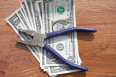Pliers and dollars Stock Image