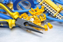 Pliers with electrical component kit on grey metal background Royalty Free Stock Photo