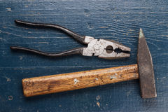 Pliers and hammer on blue table Royalty Free Stock Images