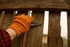 Pliers in the hand and a rusty nail in a wooden fence Stock Images